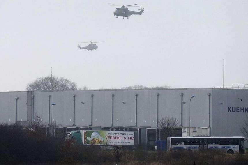 Helicopters with French intervention forces hover above the scene of a hostage taking at an industrial zone in Dammartin-en-Goele, northeast of Paris on Jan 9, 2015. -- PHOTO: REUTERS