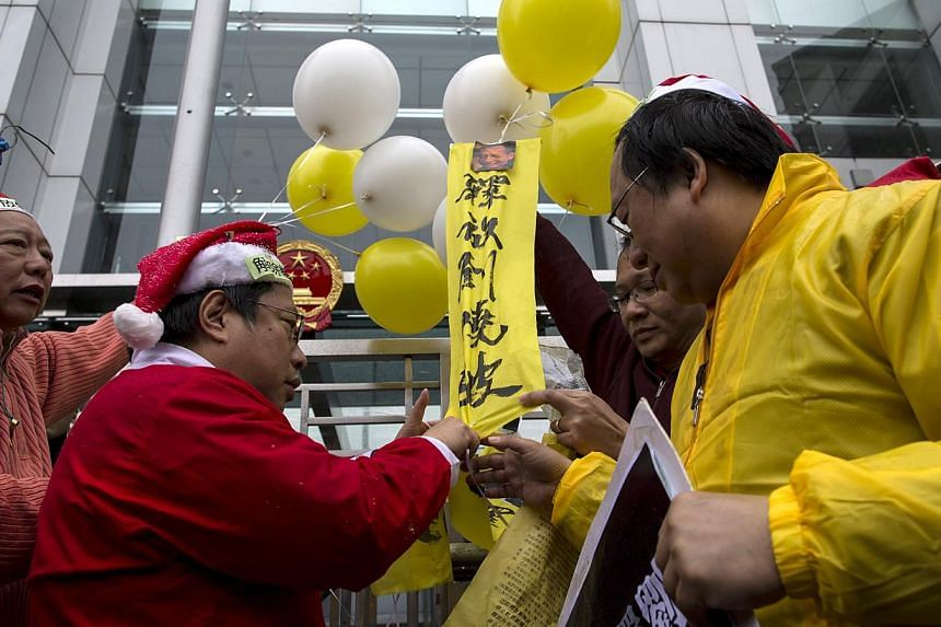 "Pro-democracy lawmakers Lee Cheuk Yan (left) and Albert Ho (second, left) hold balloons tied with slogans reading ""Release Liu Xiaobo"" and Liu's portrait during a protest to urging for release the jailed Chinese Nobel Peace Prize laureate Liu Xiaobo"