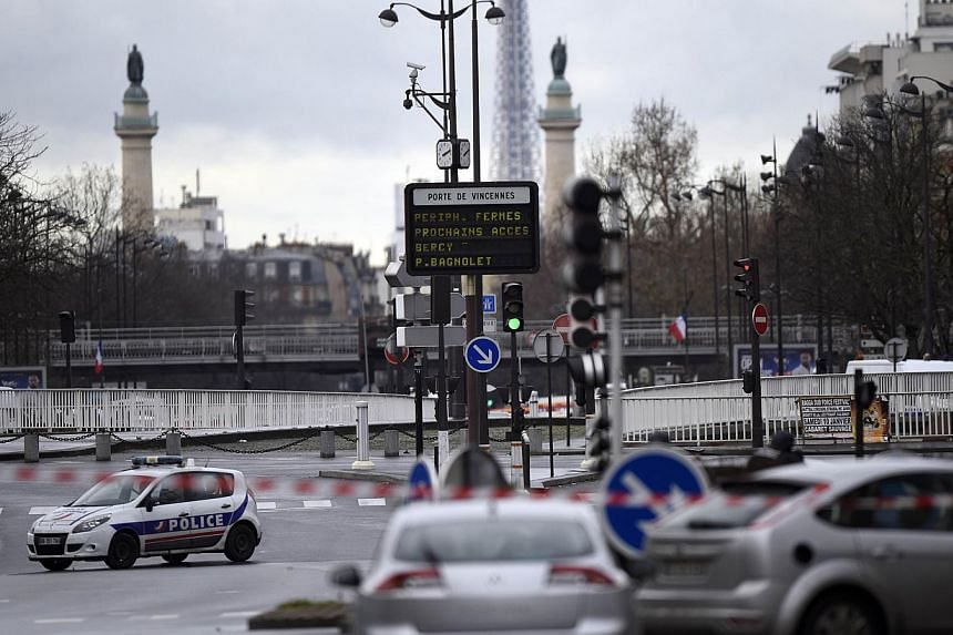 """A police car blocks the entrance to the """"peripherique"""" (circular road) at Porte de Vincennes after at least one person was injured when a gunman opened fire at a kosher grocery store in Porte de Vincennes, eastern Paris, on Jan 9, 2015, and took at l"""