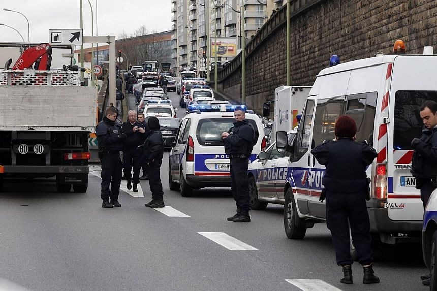 """Police forces gather together on the """"peripherique"""" (circular road) after at least one person was injured when a gunman opened fire at a kosher grocery store in Porte de Vincennes, eastern Paris on Jan 9, 2015, and took at least five people hostage,"""