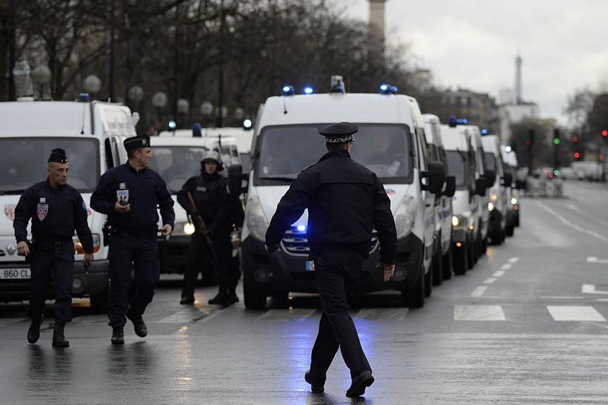 Police forces gather together at the Porte de Vincennes, eastern Paris, after at least one person was injured when a gunman opened fire at a kosher grocery store on Jan 9, 2015, and took at least five people hostage, sources told AFP. -- PHOTO: AFP