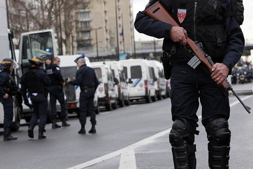 An armed member of the French riot police (CRS) takes up a position at Porte de Vincennes in Paris on Jan 9, 2015, after at least one person was injured when a gunman opened fire at a kosher grocery store and took at least five people hostage, source