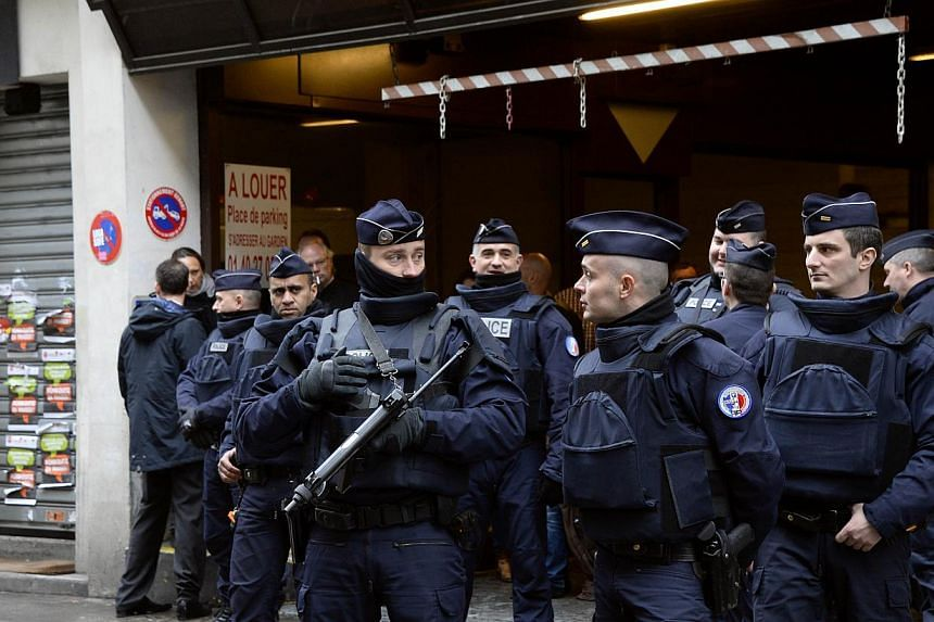 French police officers stand guard in front of the headquarters of French newspaper Liberation as editorial staff of French satirical weekly newspaper Charlie Hebdo and Liberation meet, on Jan 9, 2015, in Paris, after a deadly attack that occurred on