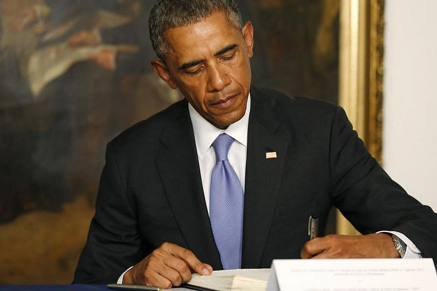 US President Barack Obama signing a condolences book at the French Embassy in Washington on Jan 8, 2015, as he pays his respects to victims of the Charlie Hebdo attack. -- PHOTO: REUTERS