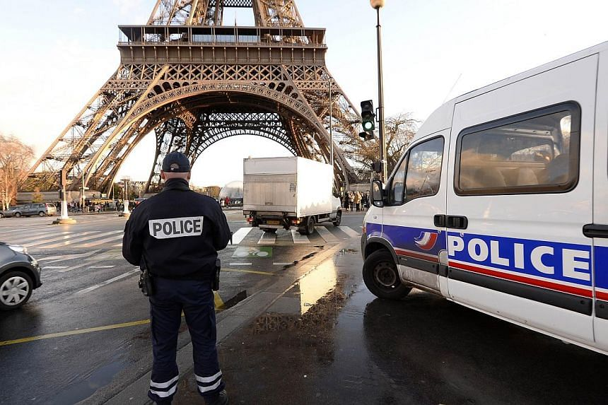 A French police officer stands in front of the Eiffel Tower on Jan 8, 2015 in Paris. Having known ties to jihadist groups is no guarantee a person will be under constant surveillance by the French authorities, experts say. -- PHOTO: AFP