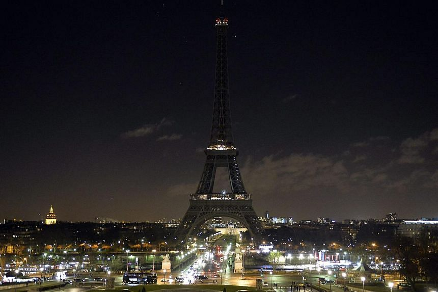 At 8pm on Jan 8, 2015, the Eiffel Tower lights were switched off for six minutes as a tribute to the victims of the Charlie Hebdo attack. -- PHOTO: REUTERS