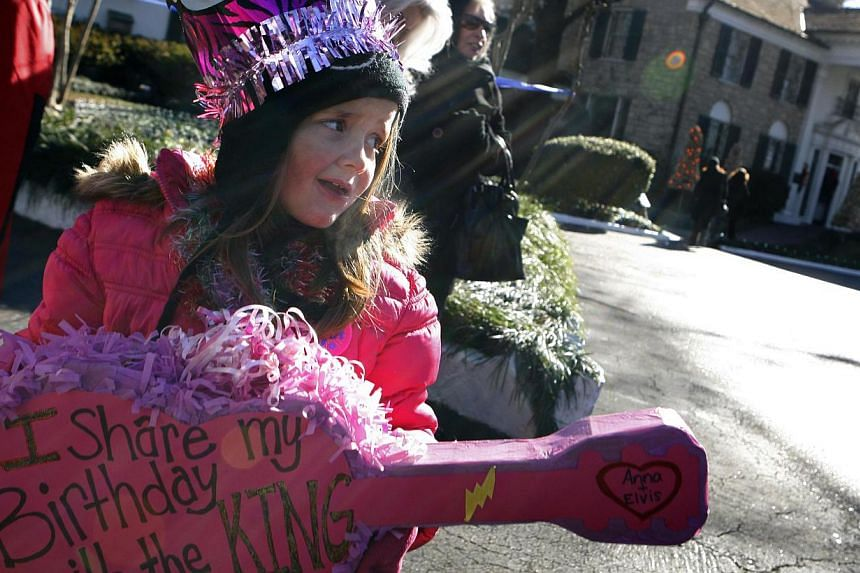 Seven-year-old Ann Dunn of Bartlett, Tennessee, holds a guitar-shaped placard during a proclamation of Elvis Presley Day by Memphis and Shelby County officials at Graceland in Memphis, Tennessee on Jan 8, 2015.-- PHOTO: REUTERS