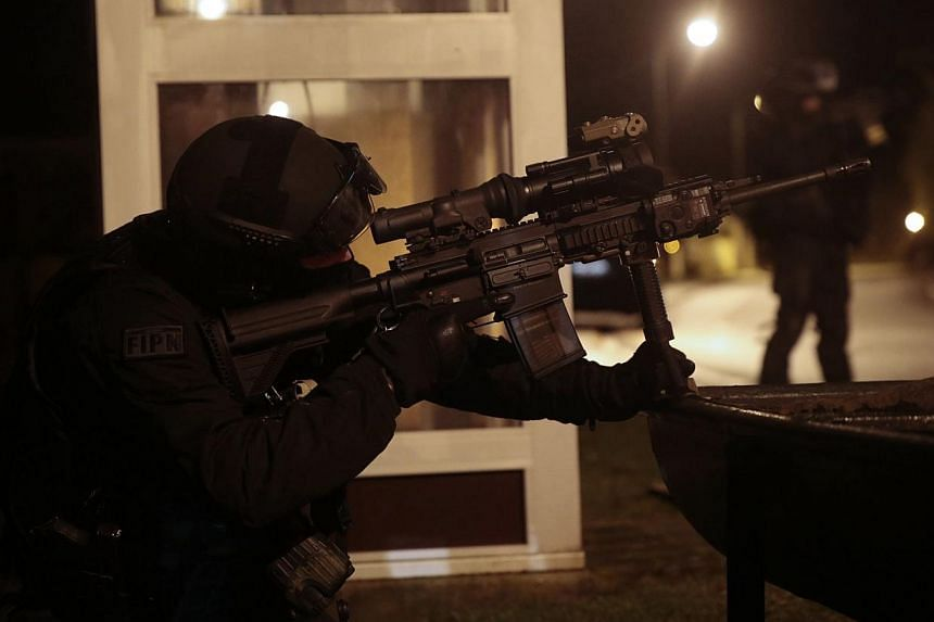 A member of the French police intervention force (GIPN) looking through the scope of his rifle as during searches in Fleury, northern France, on Jan 8, 2015. a manhunt for suspects in the deadly attack on the Paris offices of French satirical weekly