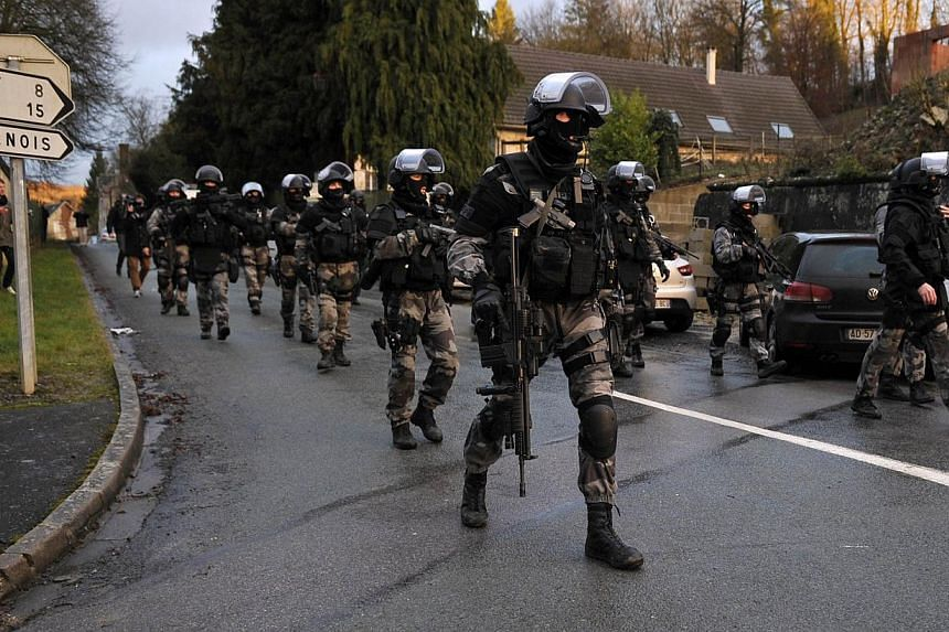 Members of GIPN and Raid, the French police special forces, walking in Corcy, northern France, on Jan 8, 2015 as they carry out searches as part of an investigation into a deadly attack the day before by armed gunmen on the Paris offices of French sa