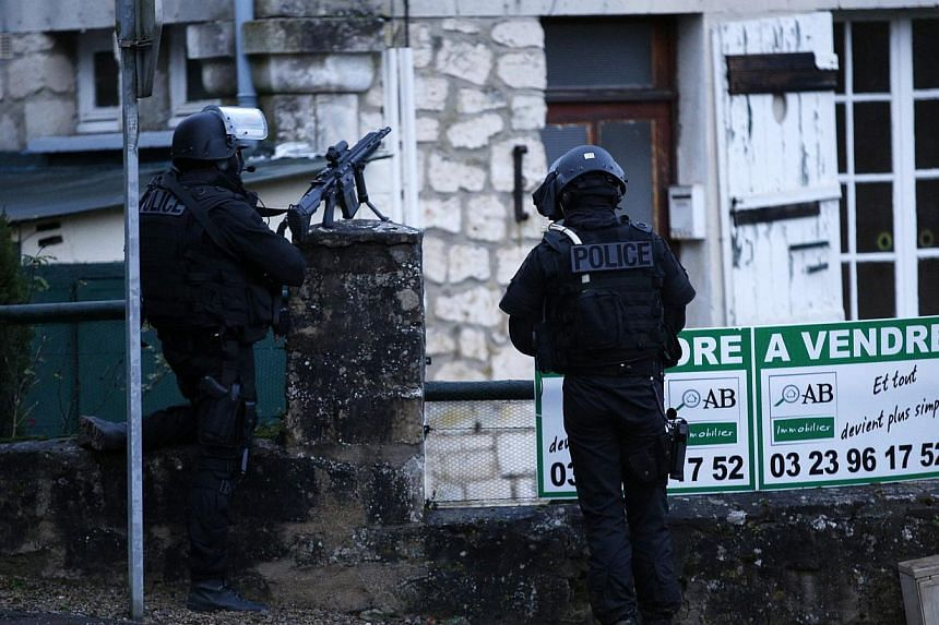 Police officers patrolling in Longpont, near Villers Cotterets, north-east of Paris on Jan 8, 2015. during the manhunt for the suspects in the Charlie Hebdo shooting. -- PHOTO: AFP