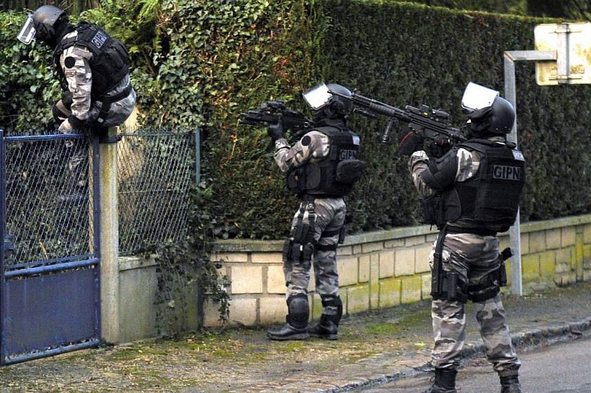 Members of the GIPN, a French police special forces, walk in Corcy, northern France, on Jan 8, 2015 carry out searches as part of an investigation into a deadly attack the day before by armed gunmen on the Paris offices of French satirical weekly Cha