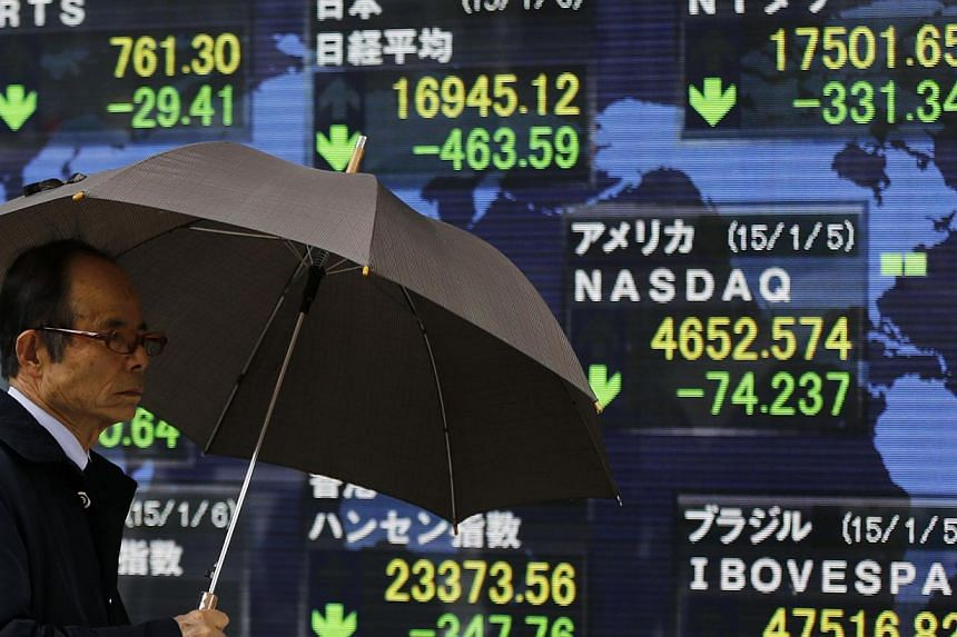 An electronic board displaying Japan's Nikkei average and various countries' stock price index outside a brokerage in Tokyo. Asian stocks gained on Friday on upbeat expectations for the closely-watched US jobs data. -- PHOTO: REUTERS