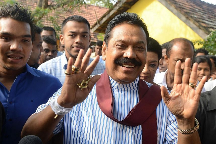 Sri Lankan President Mahinda Rajapakse (centre) waves outside a polling station in his native town of Tangalla on Jan 8, 2015. -- PHOTO: AFP