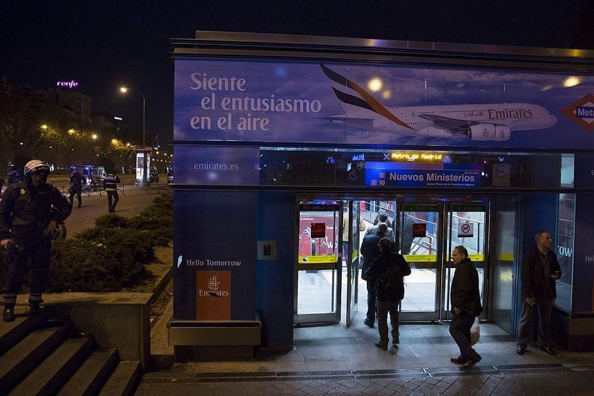 People enter Nuevos Ministerios station as a policeman watches in Madrid Jan 8, 2015. A suspicious package at Madrid's Nuevos Ministerios train station did not contain anything dangerous, a Madrid government official and police said on Thursday. -- P