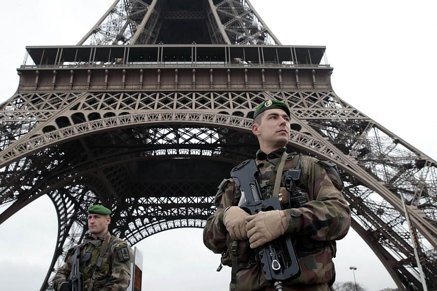 French soldiers patrol in front of the Eiffel Tower on Jan 7, 2015 in Paris.France's iconic Eiffel Tower is to go dark late on Thursday in a sombre tribute to the 12 people killed in the attack on the Paris satirical newspaper Charlie Hebdo. --