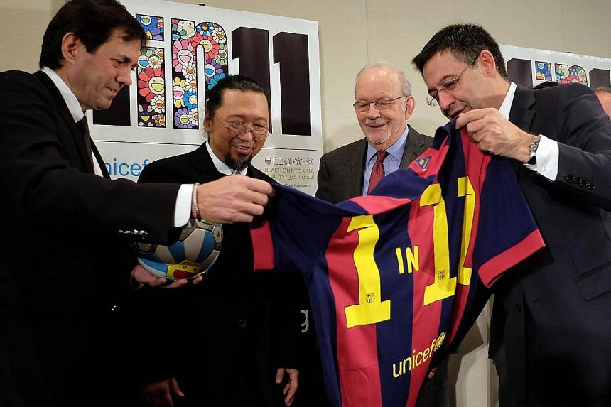 """FC Barcelona President Josep Maria Bartomeu (right) shows a jersey reading """"1 in 11"""" to artist Takashi Murak of Japan (second, left) and Unicef Executive Director Anthony Lake (second, right) during the launch the '1 in 11' campaign, in New York"""