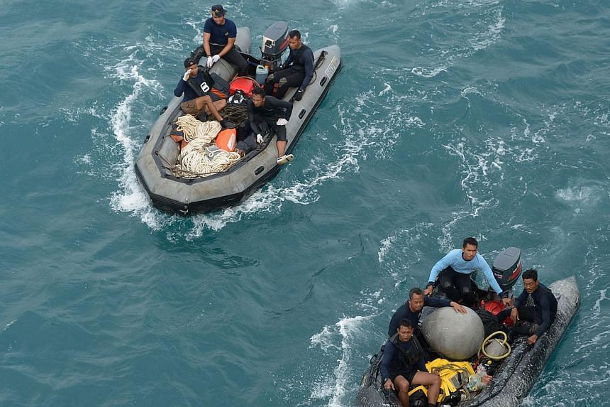 Indonesian military divers on Saturday chased faint signals believed to be from the black box data recorders of Indonesia AirAsia flight QZ8501 that crashed in stormy weather, killing all 162 people on board. -- PHOTO: AFP