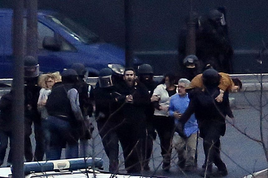 Members of the French police special forces evacuate the hostages after launching the assault at a kosher grocery store in Porte de Vincennes, eastern Paris, on Jan 9, 2015. -- PHOTO: AFP
