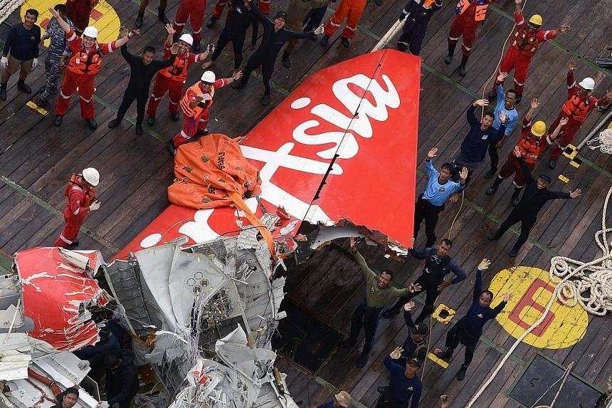 Rescuers and divers gather near the tail of AirAsia QZ8501 plane on the deck of the Indonesian Rescue ship Crest Onyx after lifted from the sea floor off Pangkalan Bun, Central Borneo, Indonesia, on  10 Jan 2015. -- PHOTO: EPA