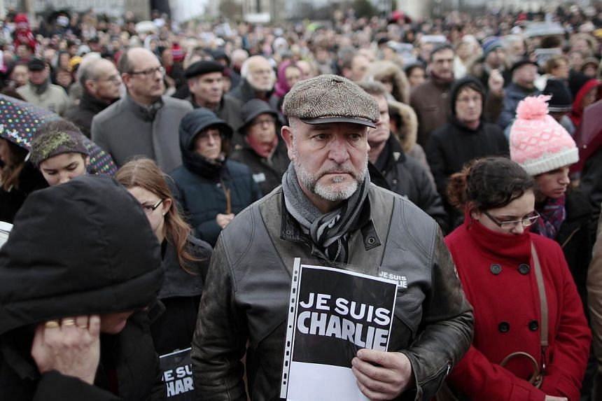 """A man hold a sign that reads, """"Je suis Charlie"""" during rally at the Memorial Square in Caen on Jan 10, 2015, as tens of thousands of people staged rallies across France authorities said, after three days of terror and twin siege dramas that claimed 1"""