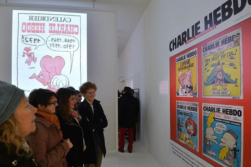 """People visit an exhibition in tribute to French satirical weekly Charlie Hebdo at the museum of French illustrator and artist Jean-Thomas """"Tomi"""" Tomi Ungerer in Strasbourg, eastern France, on Jan 9, 2015, after the deadly attack on the offices of the"""