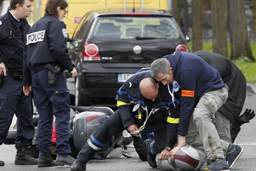 French police forcibly stop at gun point young people on a scooter as they arrive near the scene of a hostage taking at a kosher supermarket in eastern Paris on Jan 9, 2015, following Wednesday's deadly attack at the Paris offices of weekly satirical