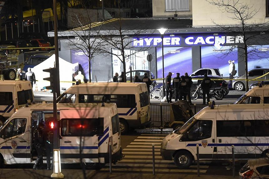 Forensic police (left) work outside the Hyper Casher kosher grocery store near Porte de Vincennes, eastern Paris, on Jan 9, 2015, after police launched an assault killing the gunman holed up in the market and freeing the hostages. -- PHOTO: AFP