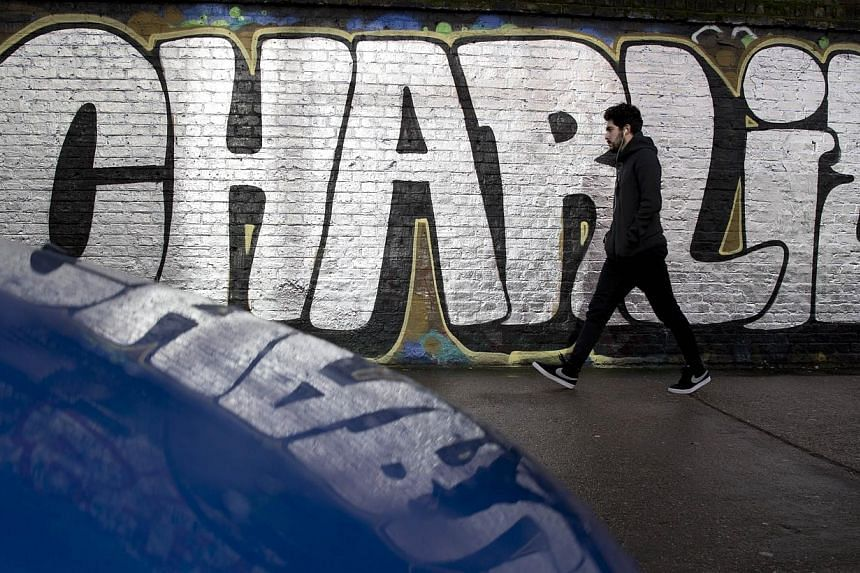 """A pedestrian walks past graffiti that reads """"[Je suis] Charlie"""" (I am Charlie), in east London on Jan 10, 2015.Hundreds in southern Afghanistan rallied to praise the killing of 12 people at the French newspaper Charlie Hebdo, calling the two gu"""