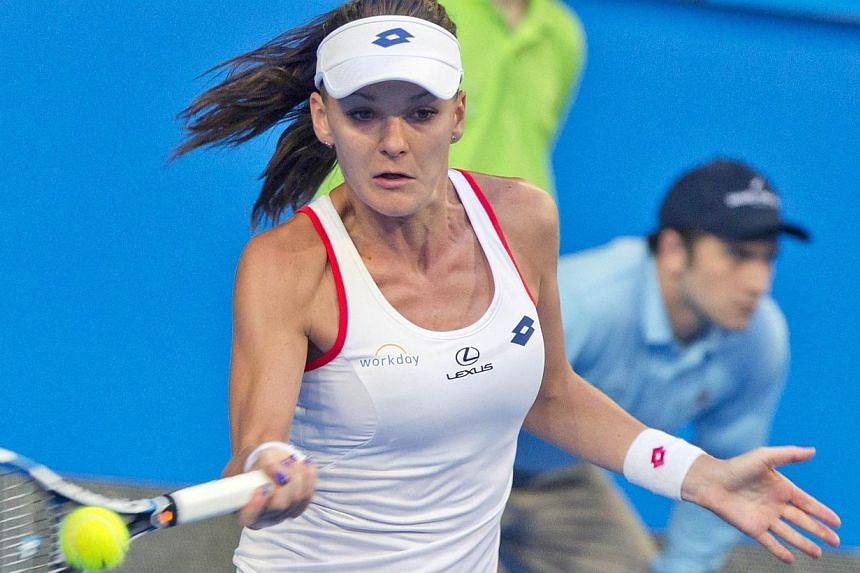 Agnieszka Radwanska of Poland hits a return against Serena Williams of the US during the final match on day seven of the Hopman Cup tennis tournament in Perth on Jan 10, 2015. -- PHOTO: AFP