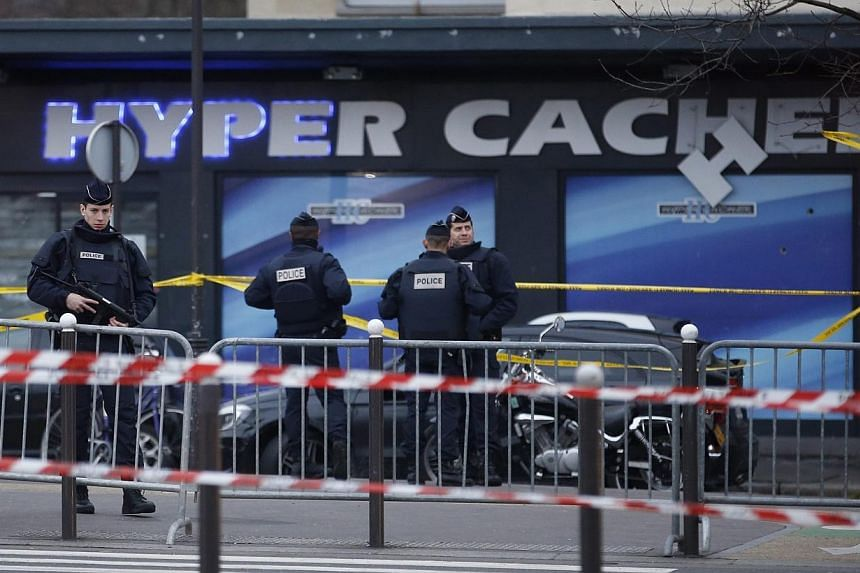 Police officers stand in front of HyperCasher supermarket at Porte de Vincennes in eastern Paris, a day after a gunman took hostages and opened fire. France is keeping its highest possible security level in the greater Paris area, Interior Minis