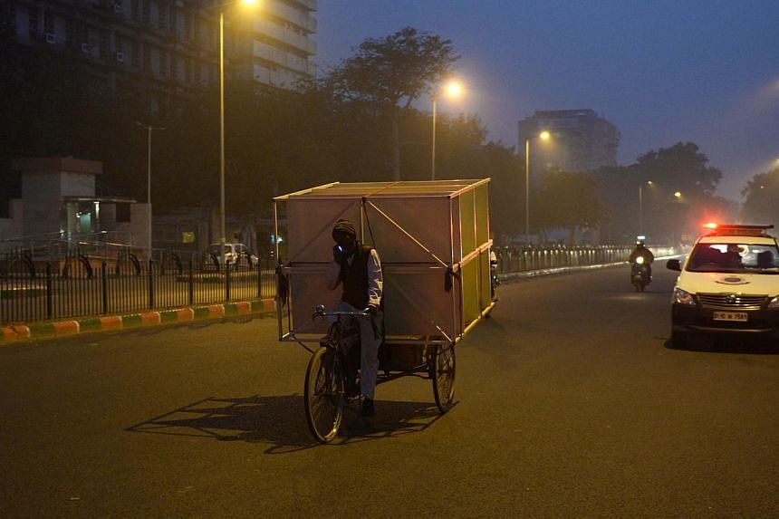 An Indian cycle rickshaw puller transports a rack of shelves as he speaks on his mobile phone at dusk in New Delhi on Jan 4, 2015. -- PHOTO: AFP