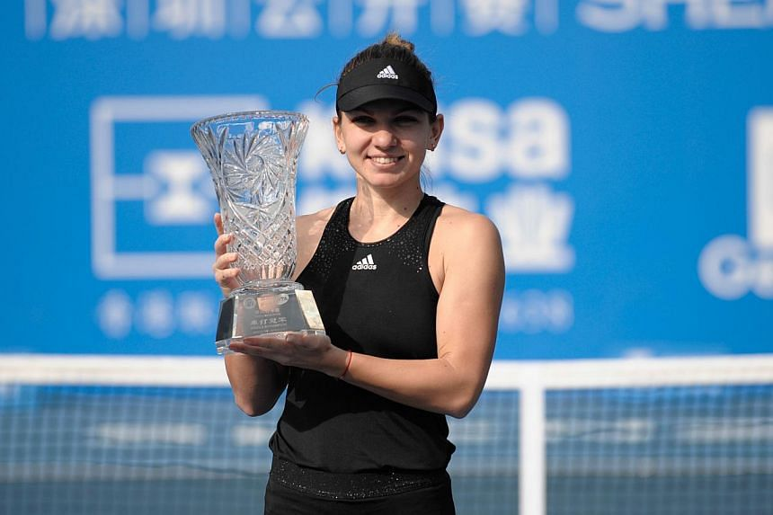 Simona Halep of Romania poses with her winner's trophy after defeating Timea Bacsinszky of Switzerland in their singles final match at the Shenzhen Open WTA Tennis tournament in Shenzhen, south China's Guangdong province on Jan 10, 2015. -- PHOTO: AF