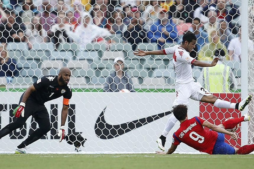 South Korea's Cho Young-cheol (right) scores a goal past Oman's goalkeeper Ali Al-Habsi (left) and Oman's Mohammed Al-Musalami during their Asian Cup Group A soccer match at the Canberra stadium in Canberra Jan 10, 2015. -- REUTERS
