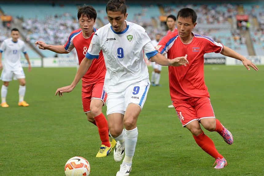 Ryang Yong Gi (left) and Jon Kwang Ik of North Korea (right) challenge Odil Akhmedov of Uzbekistan (centre) for the ball during their Group B football match of the AFC Asian Cup in Sydney on Jan 10, 2015. -- PHOTO: AFP