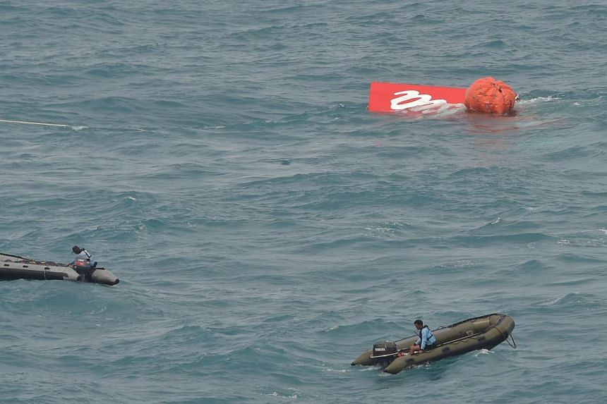 Part of the tail of AirAsia flight QZ8501 floating on the water's surface as Indonesian Navy divers conduct search operations for black boxes of the aircraft in the Java sea on Jan 10, 2015. -- PHOTO: AFP