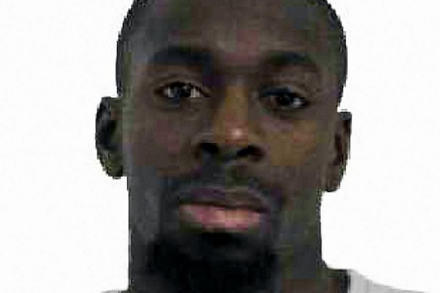 """The gunman killed by police on Friday after taking hostages at a Jewish supermarket in Paris - Amedy Coulibaly (above)- told BFMTV station he had """"coordinated"""" with the suspected Charlie Hebdo attackers and belonged to the Islamic State group."""