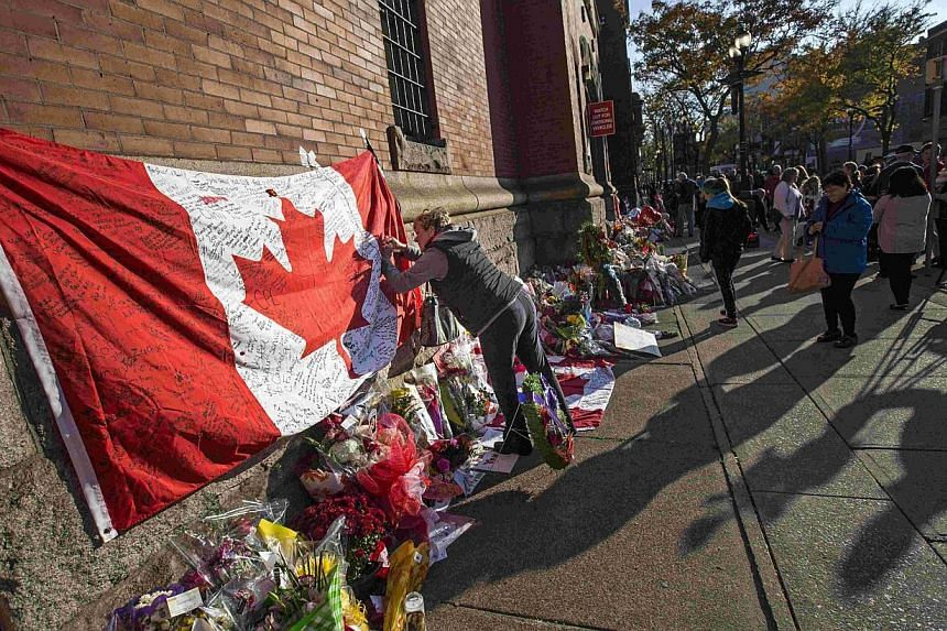 People writing messages on a Canadian flag on Oct 24, 2014, at a makeshift memorial in honour of soldier Nathan Cirillo, who was killed during a shooting at the Canada War Memorial in Ottawa on Oct 22. -- PHOTO: REUTERS