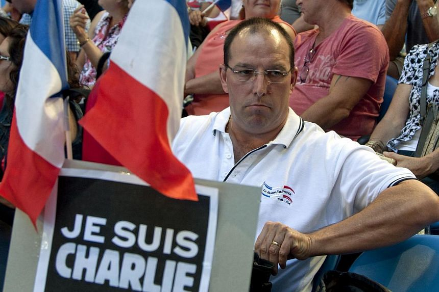 """A spectator at the Hopman Cup tennis tournament in Perth, Australia, on Jan 9, 2015, holding French flags and a placard saying """"Je Suis Charlie"""". France's Alize Cornet was playing against Poland's Agnieszka Radwanska. -- PHOTO: AFP"""