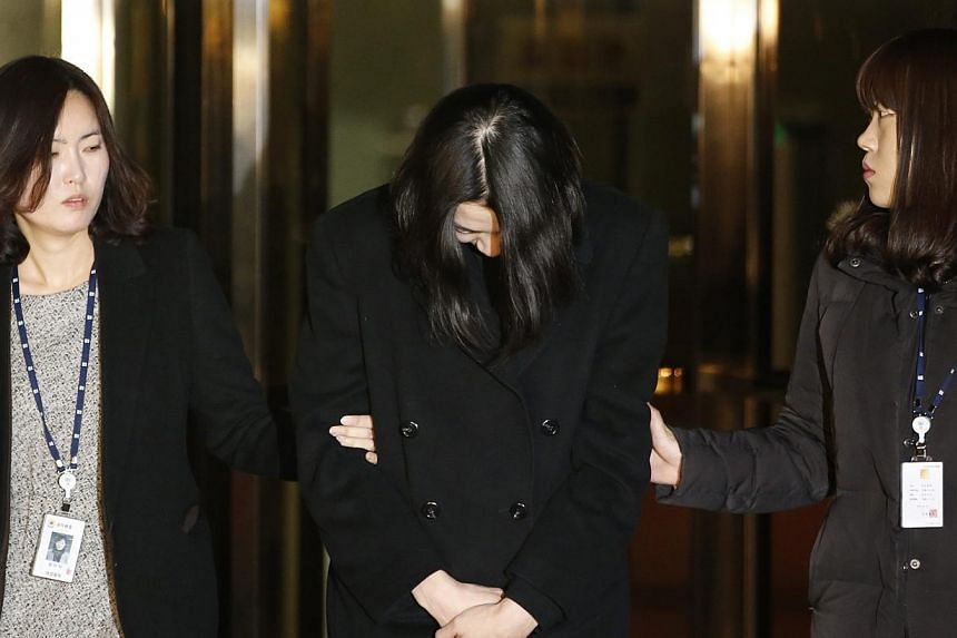 Heather Cho (centre), daughter of chairman of Korean Air Lines, Cho Yang Ho, leaves the Seoul Western District Prosecutor's office for a detention facility after a Korean court ordered her to be detained on Dec 30, 2014. -- PHOTO: REUTERS