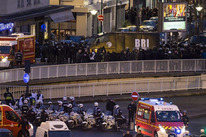 Members of the BRI police elite unit gather during an assault on the HyperCasher supermarket at Porte de Vincennes in Eastern Paris after a gunman opened fire and took hostages, on the border of Paris and its suburb Sain-Mande, on Jan 9, 2015. -- PHO