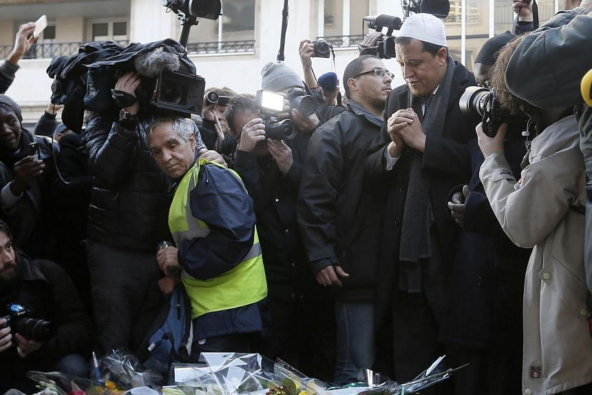 Hassen Chalghoumi (right), Imam of the municipal Drancy mosque in Seine-Saint-Denis, is surrounded by journalists as he pays his respects outside the offices of weekly satirical newspaper Charlie Hebdo in Paris Jan 8, 2015. French imams condemne