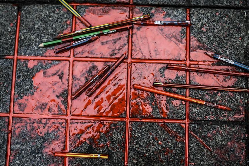Pencils with red ink are placed in front of the French Consulate in Istanbul after a demonstration for the victims of the January 7 massacre at the Charlie Hebdo magazine offices in Paris on Jan 9, 2015. -- PHOTO: AFP