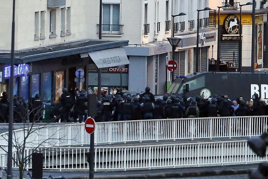 Members of the French special police forces launch the assault at a kosher grocery store in Porte de Vincennes, eastern Paris, on Jan 9, 2015. -- PHOTO: AFP