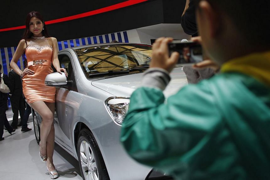 A child takes a picture of a model as she poses next to a car during the the 15th Shanghai International Automobile Industry Exhibition in Shanghai, on April 21, 2013. -- PHOTO: REUTERS