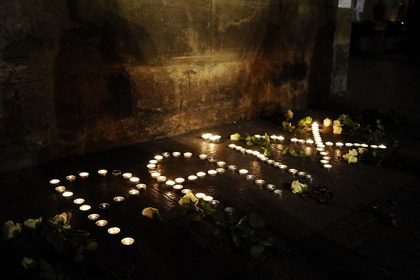 """Lit candles forming the word """"peace"""" in French outside the Capitole building in Toulouse, southern France, during a gathering to pay tribute to the victims of a deadly attack on the Paris headquarters of French satirical weekly Charlie Hebdo. A"""