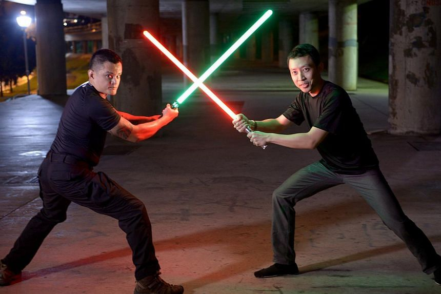Training consultant Reza Emmanuel (green lightsaber, left) and entrepreneur Kong Ming Jie (red lightsaber, right) are founders of the Saber Authority, which imports lightsabers and teaches duelling classes. -- ST PHOTO: LIM SIN THAI