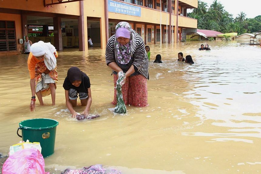 Washing clothes and children playing at Kuala Krau Primary School. Flood-affected Schools in Malaysia may have reopened, but lessons are still a long way off with no books, tables and chairs, running water and power available. -- PHOTO: THE STAR
