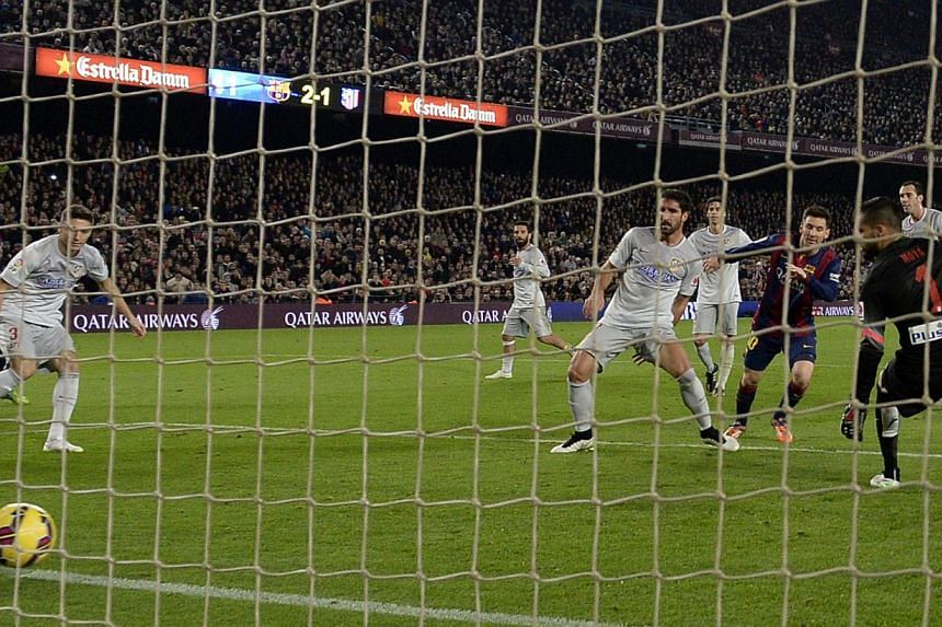 Barcelona's Argentinian forward Lionel Messi scores his side's third and final goal.-- PHOTO: AFP