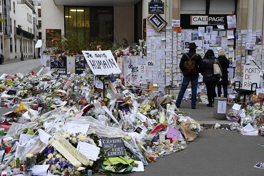 People visit a makeshift memorial near the Paris headquarters of the French satirical weekly Charlie Hebdo on Jan 12, 2015, in tribute to the 17 victims of a three-day killing spree by homegrown Islamists.This week's edition will defiantly feat