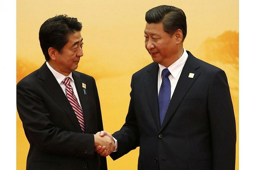 Japan's Prime Minister Shinzo Abe (left) shakes hands with China's President Xi Jinping during the welcoming ceremony at the Asia Pacific Economic Cooperation (APEC) forum, inside the International Convention Center at Yanqi Lake, in Beijing, on Nov